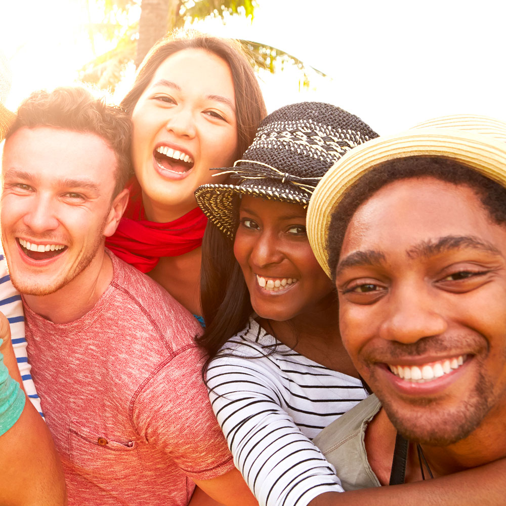 Four Friend of different ethnicity smiling and laughing at the camera