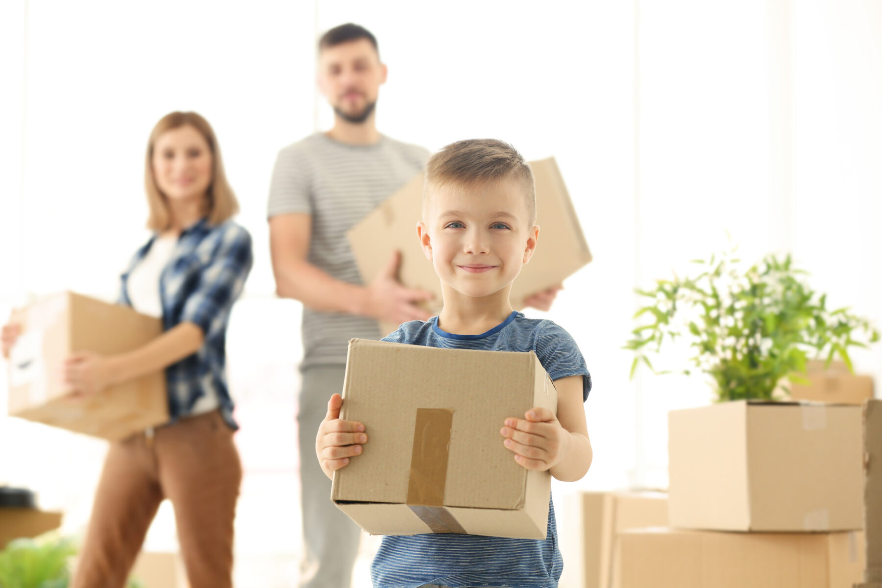 family moving boxes with little boy holding box and smiling at the camera